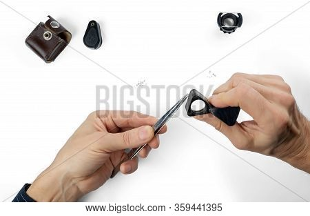A Diamond Appraisal. Hands Of The Appraiser With A Magnifying Glass And Tweezers. Isolated On White