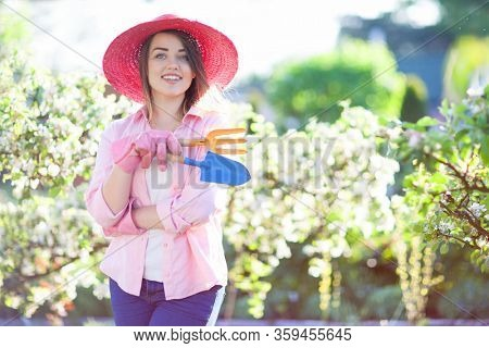 Smiling woman standing with gardening tools in an orchard