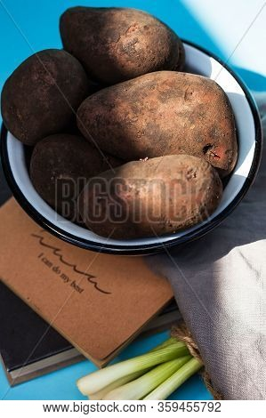 Unwashed Potatoes In A White Bowl On A Blue Background. Photo For Food Markets, A Menu For Vegetaria