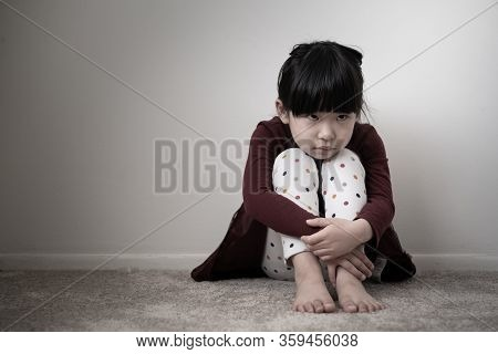 Lonely Sad Young Girl Is Sitting In The Corner Wall And Holding Her Knees, Concept Of Domestic Viole