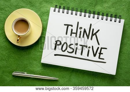 Think positive inspirational handwriting in a sketchbook with a cup of coffee, positivity, optimism and mindset concept