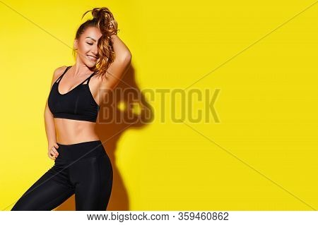 Sexy Lady Workout Studio Portrait In Black Sport Wear On Yellow Background, Fitness Sporty Woman Bea