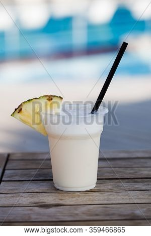 A Pina Colada Cocktail With A Pineapple Slice On A Wooden Table Against The Backdrop Of An Outdoor B