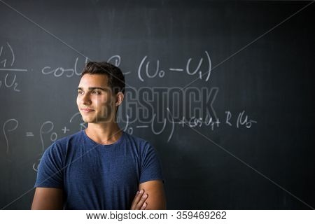 Students in a classroom - handsome student solving a math problem on a blackboard during math class