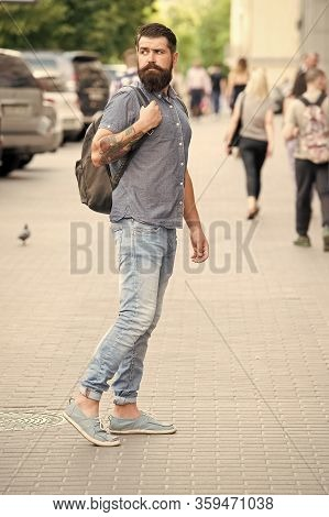 Hipster Wearing Backpack Urban Street Background. Bearded Man Travel With Backpack. Guy Exploring Ci