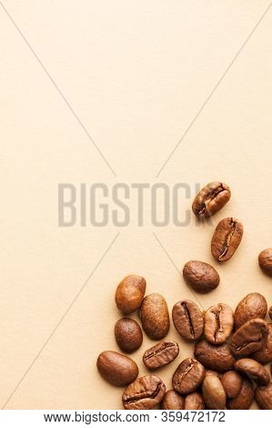 A Handful Of Arabica Coffee Beans On A Brown Background. Vertical Photo With Place For Text For Roas