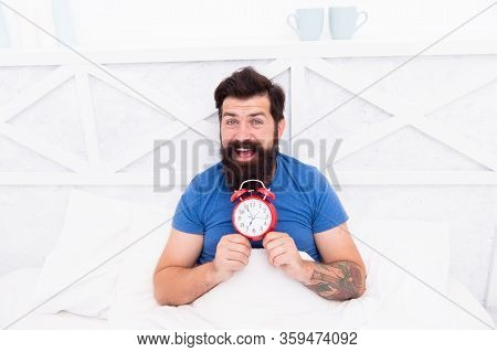 Happy Wake Up Of Man Lying In Bed With Alarm Clock. Guy Is Waking Up. Alarm Clock In The Morning. Ma