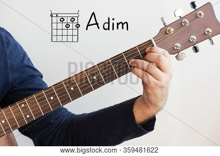Learn Guitar - Man In A Dark Blue Shirt Playing Guitar Chords Displayed On Whiteboard, Chord A Dim