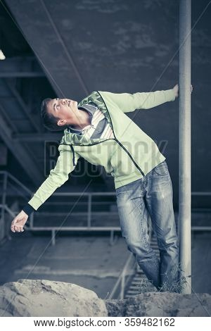 Happy fashion teen boy walking outdoor Stylish trendy male model in light green hoodie and dark blue jeans