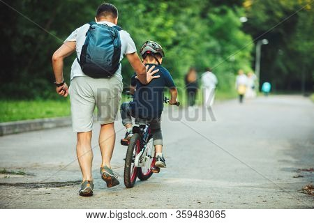 Father Teaching Son How To Ride Bicycle