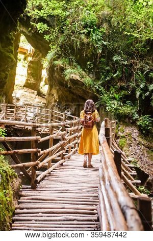 Young Gorgeous Woman In Yellow Sundress Near Waterfall Walking By Wooden Footpath Leading To Caves
