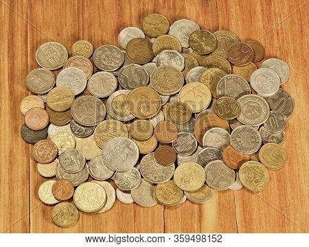 Various Coins Of World On Wooden Background Taken Closeup.