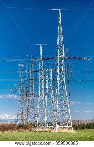 Electricity Transmission Pylons In A Row And Blue Sky