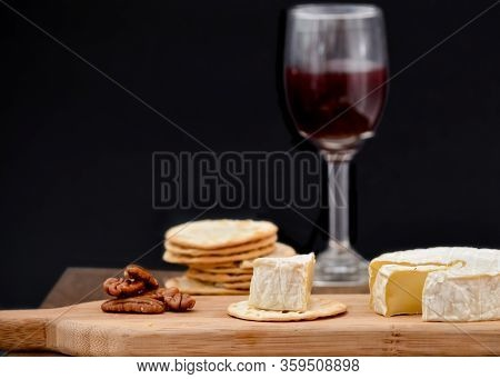 Brie And Pecan Halves On Wooden Cheese Board, Accomplained By Crackers And One Glass Of Red Wine, Ag