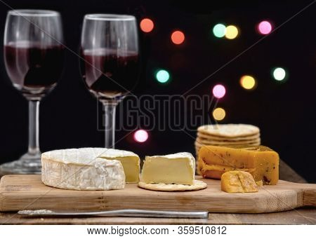 Brie And Hot Pepper Jack Cheese On Wooden Cheese Board, Accomplained By Crackers And Two Glasses Of