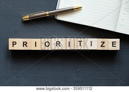 Modern Business Buzzword - Prioritize. Top View On Wooden Table With Blocks. Top View. Close Up.