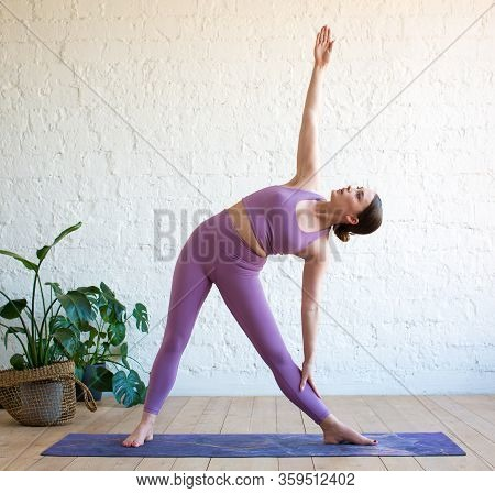 Young Attractive Yogi Woman Practicing Yoga, Doing Utthita Trikonasana Exercise, Extended Triangle P