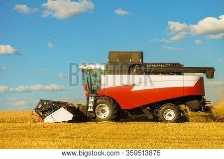 Combine Harvester In The Field During The Harvest. Side View.