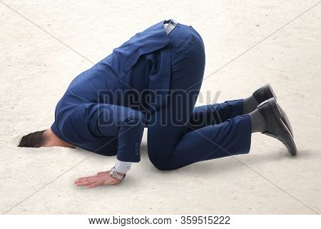The businessman hiding his head in sand escaping from problems