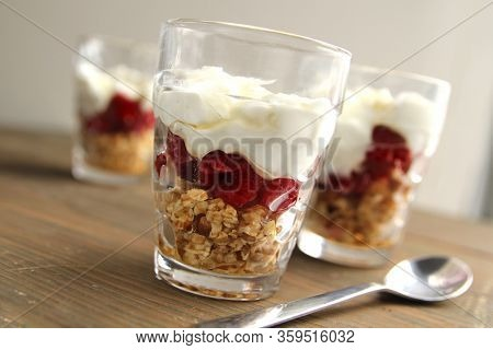 Delicious plain yogurt with nuts and a berry coulis in a jar on a wooden background