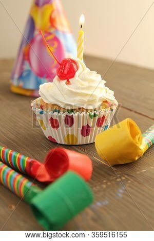 Vanilla cupcake with white frosting, cherry on top and a candle with party hat and blowers for birthday party