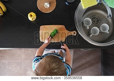 Small Vegetarian Child Cuts Big Green Cucumber With Knife, Vegan Kid Helper Cooks Vegetable Salad In
