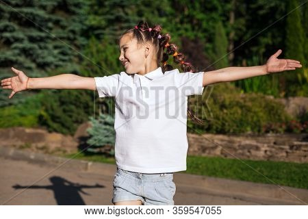 Joyful Child Girl With Pigtails Waving On The Wind Wearing White Shirt Running Spreading Hands In A