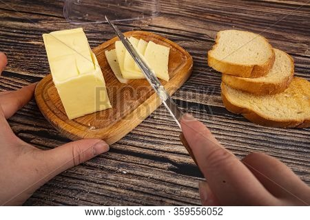 Someone Cuts Some Butter With A Knife From A Piece Of Butter In A Wooden Butter Dish And Fresh Wheat