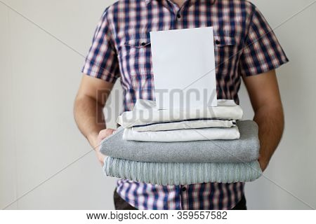 Housework And Cleaning. Laundry Day. Male Hands With Stack Of Washed Clothes And Laundry Detergent B
