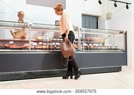 Back View Of Fasionable Lady Looking And Choosing Fresh Meat In Store. Cheerful Senior Male Butcher