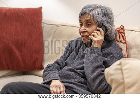 Old Elderly, British Asian Woman Talking On A Phone, Self Isolating During Coronavirus Outbreak Lock