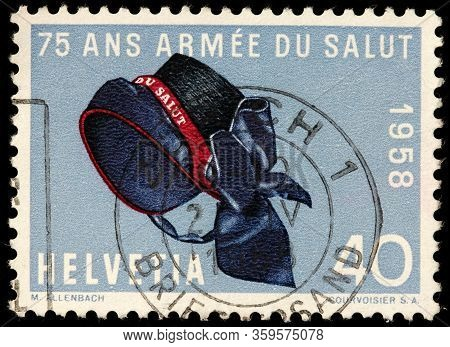 Luga, Russia - October 20, 2019: A Stamp Printed By Switzerland Shows Hat Of The Salvation Army - Pr