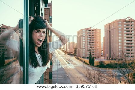 Desperate Bored Woman Peeks Out The Window During Quarantine Over Covid-19 Crisis. Stay At Home Conc