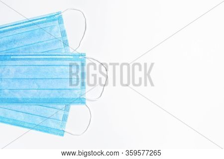 Three Blue Medical Masks On A Light Background. Flat Lay. Medical Background. Copy Space