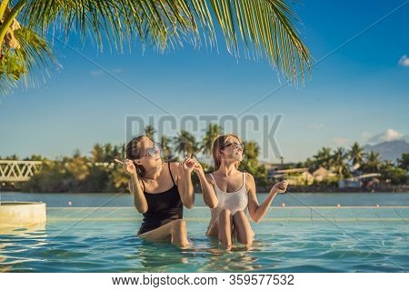 Two Beautiful Young Woman Sitting By The Poolside Of A Resort Swimming Pool During Summer Holiday. P