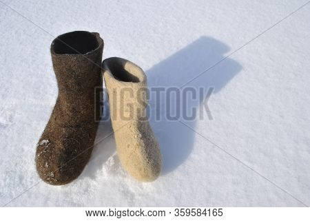 Boots Of Different Colors Stand In The Snow. Boots Top View. White And Brown Shoes. Valenoks Are Cov
