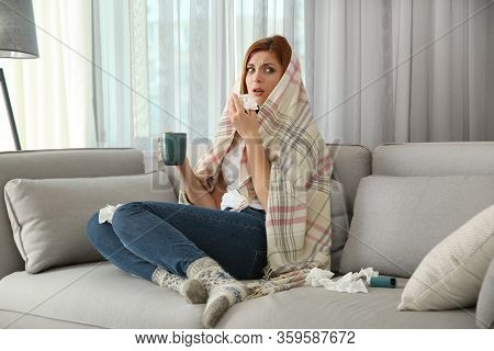 Sick Woman Wrapped In Plaid With Cup Of Hot Drink At Home. Influenza Virus
