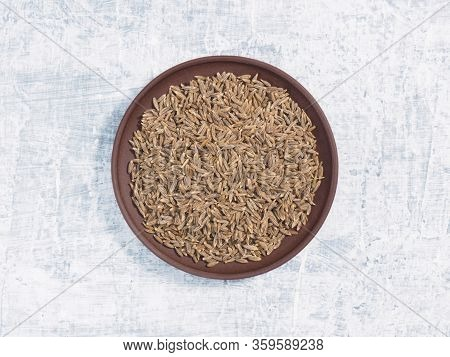 Cumin (jeera) In Clay Plate On White Concrete Background