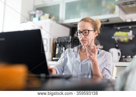 Stay At Home And Social Distancing. Woman In Her Casual Home Clothing Working Remotly From Kitchen D