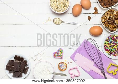 Ingredients And Utensils For Baking Cakes. Eggs, Flour, Milk, Sugar, Nuts, Chocolate And Candies On