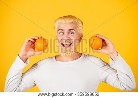 Smiling Funny Man With Oranges In Hands. Handsome Young Man Hold Fresh Natural Orange. Man Enjoying
