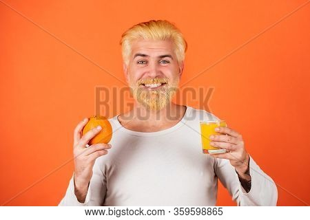 Man With Oranges And Orange Juice In Hands. Handsome Young Man Hold Fresh Natural Orange On Orange B
