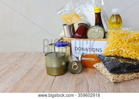 Donations Box With Canned Food On Wooden Table Background / Pasta Canned Goods And Dry Food Non Peri