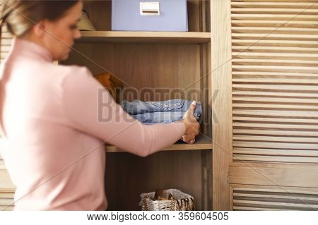 Young Brunette Girl Folds Her Clothes And Puts Them Into Cupboard And Boxes. Nordic Style Minimalism