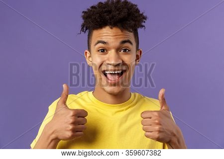 Close-up Portrait Of Enthusiastic, Lively Hipster Guy With Afro Haircut Agree With Something, Show T
