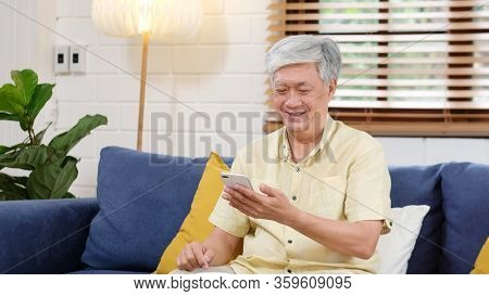 Senior Asian Man Using Mobile Phone At Home Living Room Background, Happy Retirement Asia Male Holdi