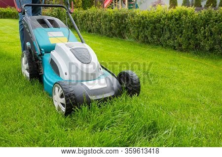 A Man Mowing Grass With A Lawn Mower In The Garden On A Sunny Day. A Lawn Mower On The Lawn, A Close