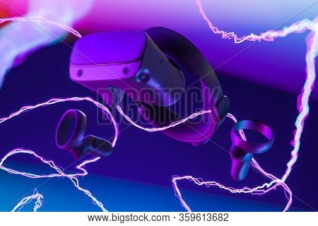 Virtual Reality Helmet Isolated On Violet And Blue Background Illuminated By Neon Light. Virtual Rea