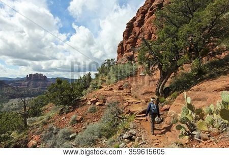 A Woman Hikes The Airport Loop Trail, Sedona, Arizona, Usa, Famous Cathedral Rock On The Left