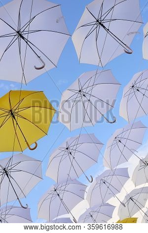 Yellow And White Umbrellas Open Against The Blue Sky